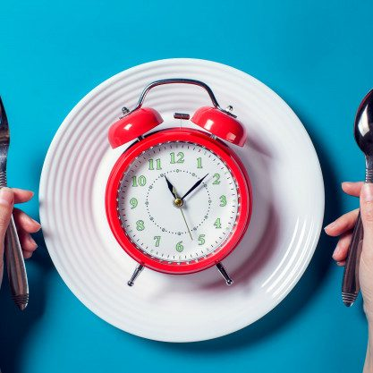 red alarm clock white plate with spoon fork color background food diet
